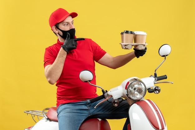 Vista dall'alto del ragazzo delle consegne fiducioso che indossa guanti uniformi e cappello in mascherina medica che si siede sullo scooter che mostra gli ordini