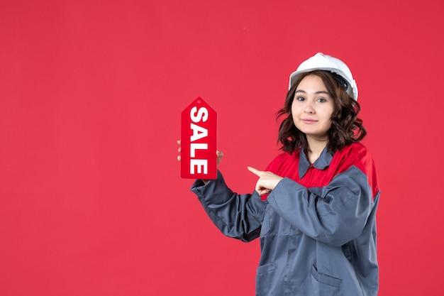 Vista dall'alto del costruttore femminile sicuro in uniforme che indossa elmetto e mostra l'icona di vendita su sfondo rosso isolato