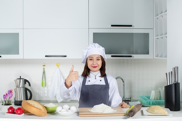 Top view of confident female chef in uniform standing behind the table with cutting board bread vegetables making ok gesture in the white kitchen
