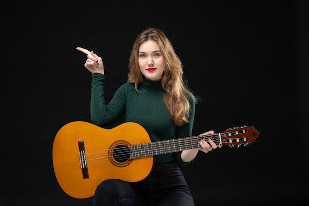Top view of confident female musician holding guitar and pointing something on the right side on black