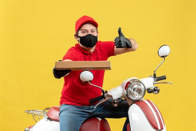 Vista superiore dell'uomo fiducioso corriere felice che indossa guanti di camicetta e cappello rossi nella mascherina medica che si siede sullo scooter che mostra l'ordine con i pollici in su
