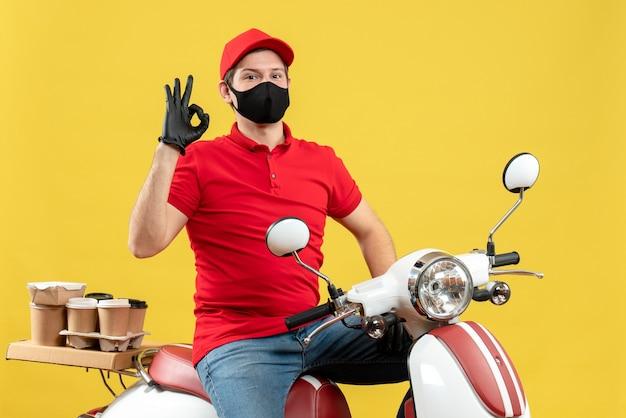 Vista dall'alto di fiducioso orgoglioso giovane adulto che indossa camicia rossa e guanti cappello in maschera medica offrendo ordine seduto su uno scooter che fa il gesto perfetto su sfondo giallo