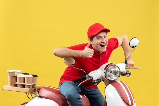 Top view of confident young adult wearing red blouse and hat delivering orders making ok gesture on yellow background