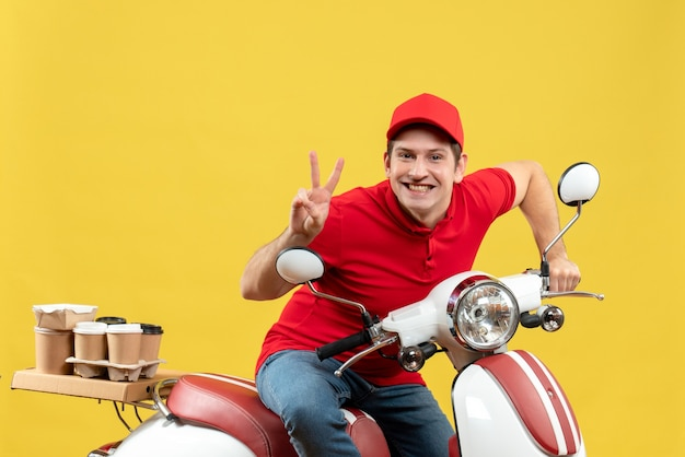Top view of confident young adult wearing red blouse and hat delivering orders making victory gesture on yellow background