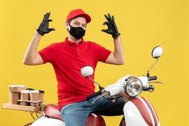 Vista dall'alto di fiducioso giovane adulto che indossa camicetta rossa e guanti cappello in maschera medica offrendo ordine seduto su uno scooter che spiega qualcosa su sfondo giallo