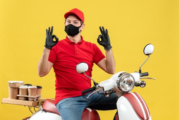 Vista dall'alto di fiducioso giovane adulto che indossa camicia rossa e guanti cappello in mascherina medica offrendo ordine seduto su scooter che fa gesto di occhiali su sfondo giallo