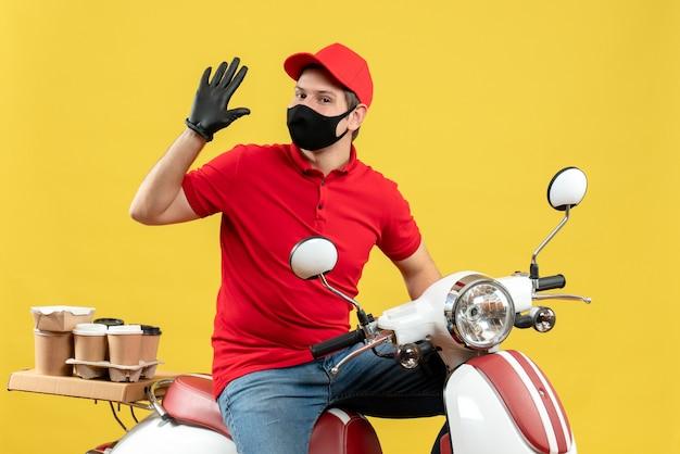 Vista dall'alto di fiducioso giovane adulto che indossa camicia rossa e guanti cappello in maschera medica offrendo ordine seduto su uno scooter che mostra cinque su sfondo giallo