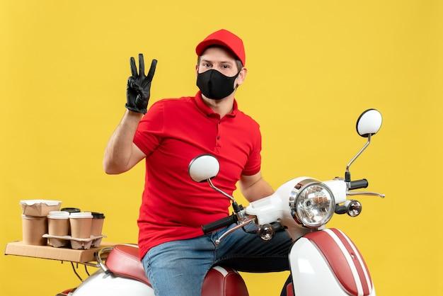 Vista dall'alto di fiducioso giovane adulto che indossa camicia rossa e guanti cappello in maschera medica offrendo ordine seduto su uno scooter che mostra tre su sfondo giallo
