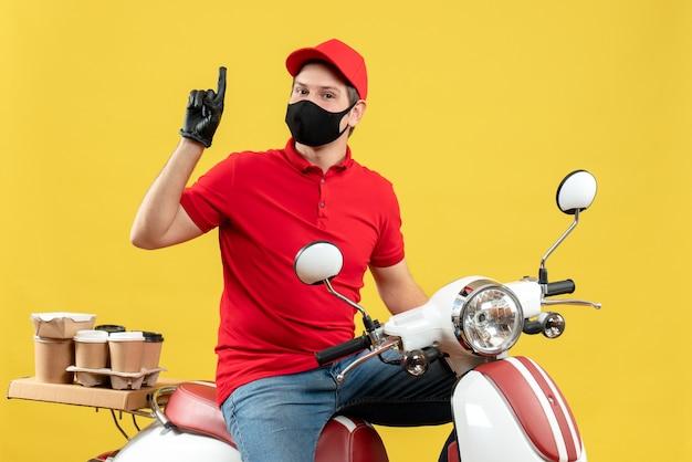 Vista dall'alto di fiducioso giovane adulto che indossa camicia rossa e guanti cappello in maschera medica offrendo ordine seduto su scooter che mostra su sfondo giallo