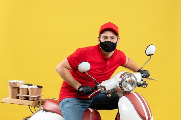 Vista dall'alto di fiducioso giovane adulto che indossa camicia rossa e guanti cappello in maschera medica offrendo ordine seduto su scooter su sfondo giallo
