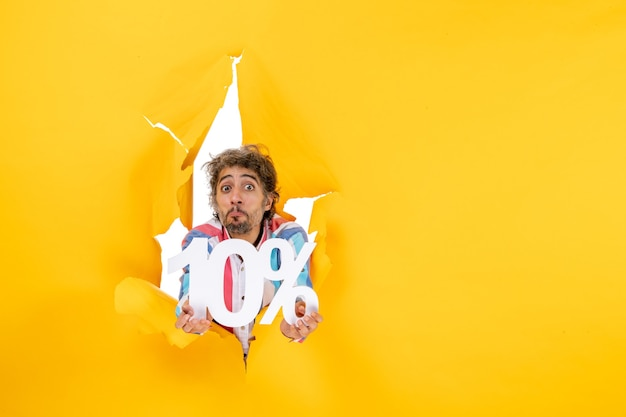 Top view of confused bearded man showing ten percentage in a torn hole in yellow paper