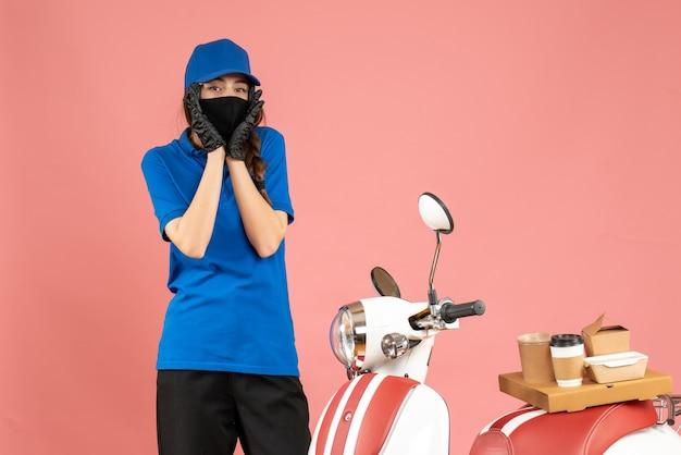 Vista dall'alto della ragazza del corriere confusa che indossa guanti con maschera medica in piedi accanto alla moto con una torta di caffè su di esso su sfondo color pesca pastello