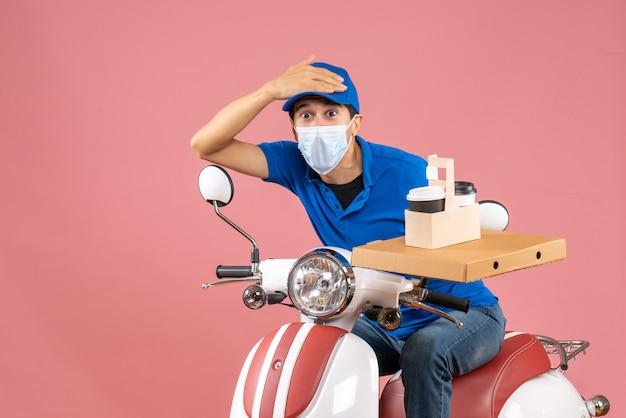 Vista dall'alto del corriere confuso in maschera medica che indossa un cappello seduto su uno scooter che tiene un documento su sfondo color pesca pastello