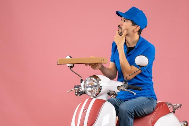 Vista dall'alto del corriere confuso in maschera medica che indossa un cappello seduto su uno scooter che tiene l'ordine su sfondo color pesca pastello