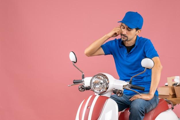 Vista dall'alto del corriere confuso che indossa un cappello seduto su uno scooter che consegna ordini su sfondo color pesca pastello