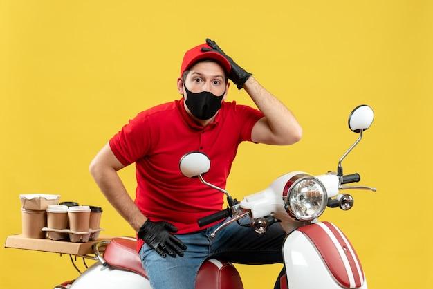 Vista dall'alto del ragazzo di corriere confuso che indossa guanti di camicetta e cappello rossi nella mascherina medica che consegna l'ordine che si siede sul motorino