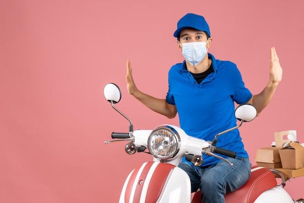 Vista dall'alto dell'uomo corriere confuso in maschera medica che indossa un cappello seduto su uno scooter su sfondo color pesca pastello