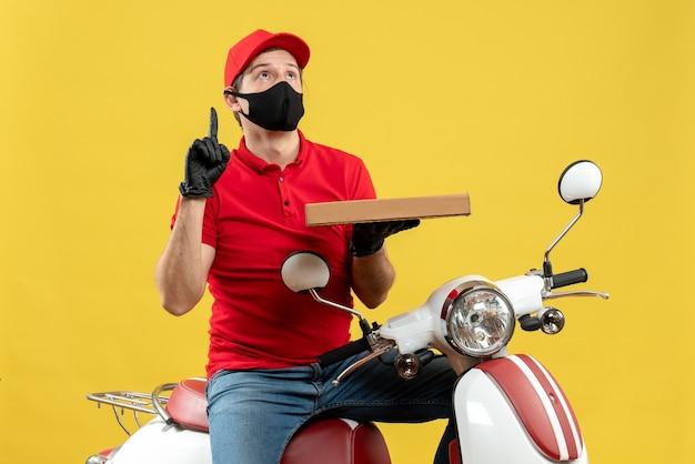 Vista superiore dell'uomo confuso del corriere che indossa guanti rossi della camicetta e del cappello nella mascherina medica che si siede sull'ordine della tenuta dello scooter con il pollice in su
