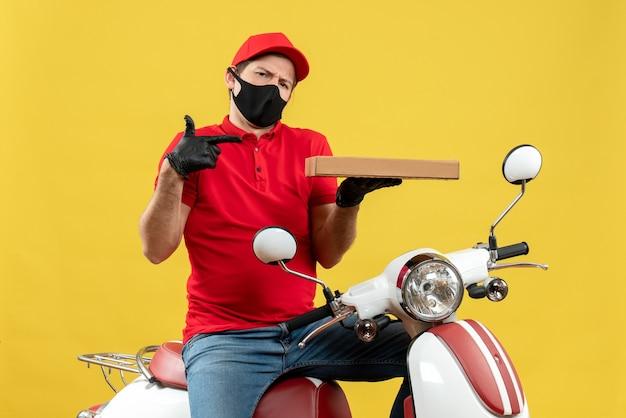 Vista dall'alto del corriere confuso uomo che indossa guanti di camicetta e cappello rossi nella mascherina medica che si siede sull'ordine di puntamento del motorino