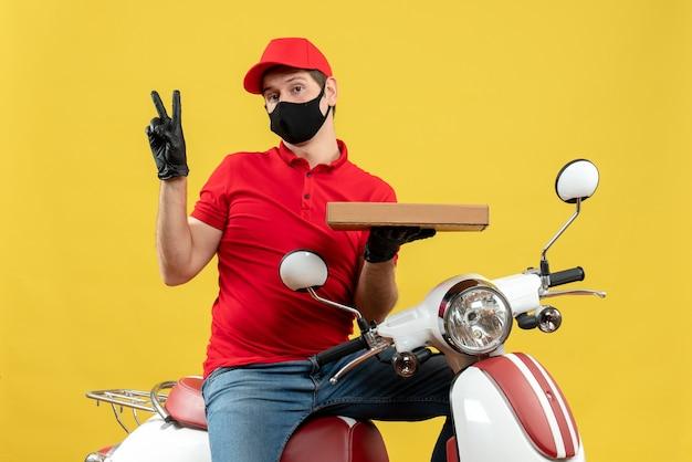Vista superiore dell'uomo confuso del corriere che indossa guanti rossi della camicetta e del cappello nella mascherina medica che si siede sullo scooter che mostra l'ordine che fa il gesto di vittoria