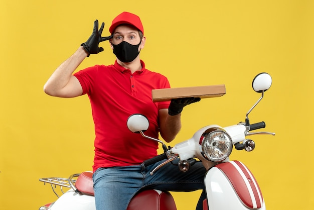 Vista dall'alto del corriere confuso uomo che indossa camicetta rossa e guanti cappello in mascherina medica che si siede sullo scooter che mostra ordine