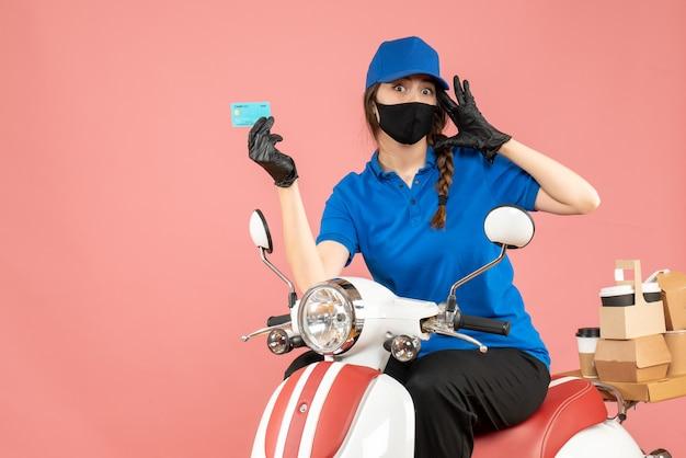 Vista dall'alto della donna corriere confusa che indossa maschera medica e guanti seduta su scooter con in mano una carta di credito che consegna ordini su sfondo pesca pastello peach