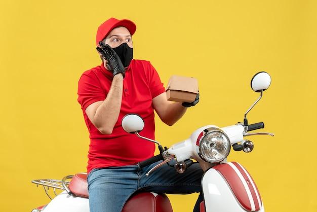 Vista dall'alto del ragazzo delle consegne confuso indossando guanti uniformi e cappello in maschera medica che si siede sullo scooter che mostra l'ordine