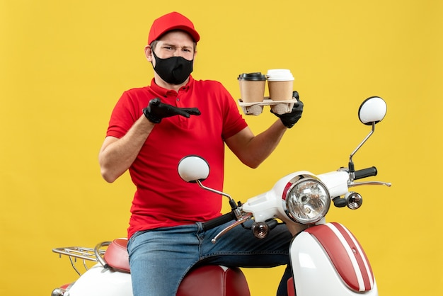 Top view of confused delivery man wearing uniform and hat gloves in medical mask sitting on scooter showing orders