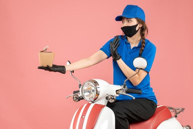 Vista dall'alto del fattorino confuso che indossa maschera medica e guanti seduto su uno scooter che consegna ordini su sfondo color pesca pastello