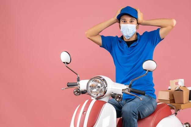 Vista dall'alto del ragazzo delle consegne emotivo confuso in maschera medica che indossa un cappello seduto su uno scooter su sfondo color pesca pastello