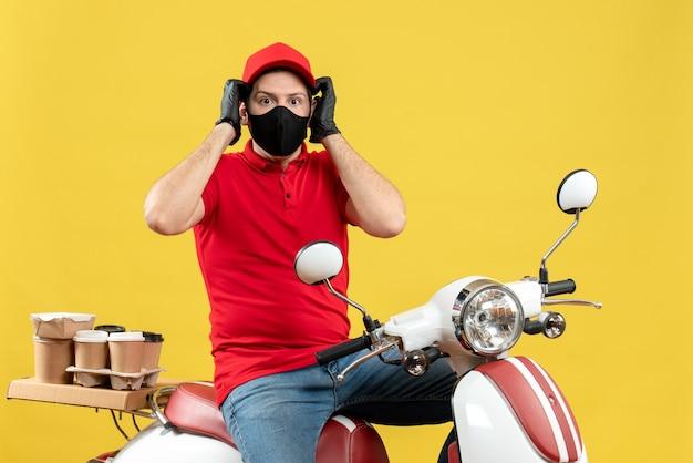 Vista superiore del giovane adulto emotivo confuso che indossa guanti di camicetta e cappello rossi nella mascherina medica che consegna l'ordine che si siede sul motorino su fondo giallo