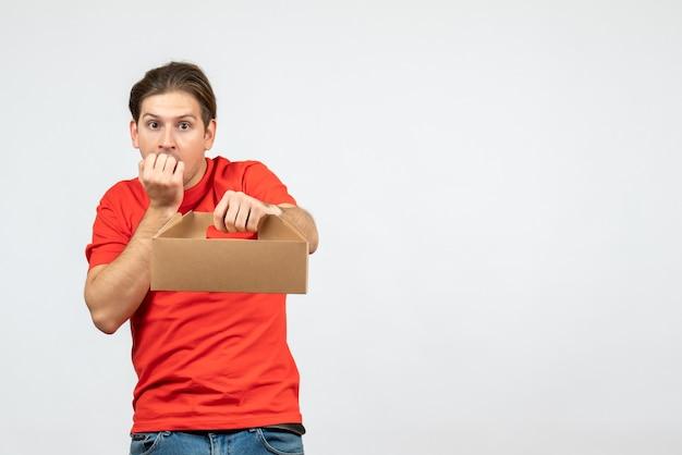 Vista dall'alto del giovane confuso ed emotivo in camicetta rossa che tiene scatola su sfondo bianco