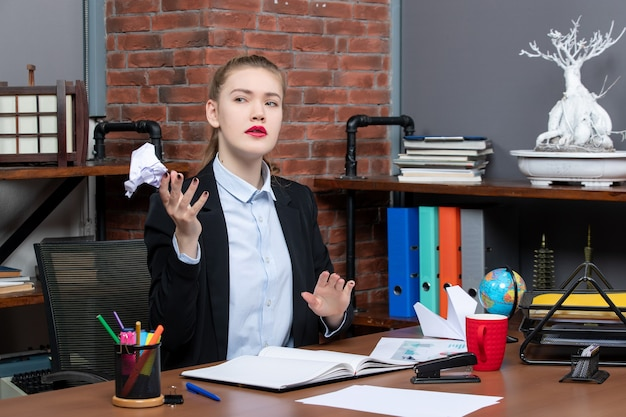 Top view of confused woman sitting at a table and holding wrapped paper in the office