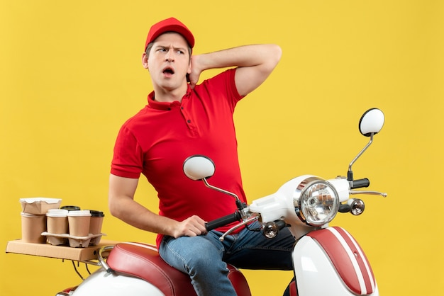 Top view of confused young adult wearing red blouse and hat delivering orders on yellow background