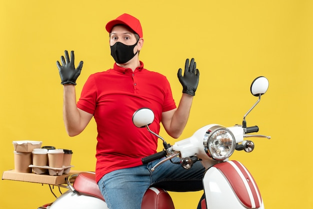Vista superiore del giovane adulto confuso che indossa guanti rossi della camicetta e del cappello nella mascherina medica che trasporta l'ordine che si siede sul motorino su fondo giallo
