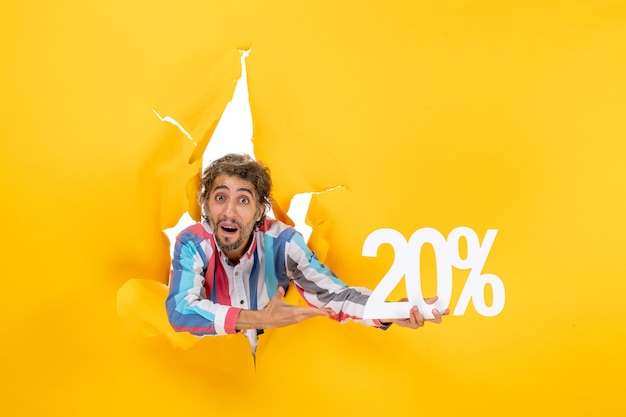 Top view of confused young man pointing twenty percentage in a torn hole in yellow paper