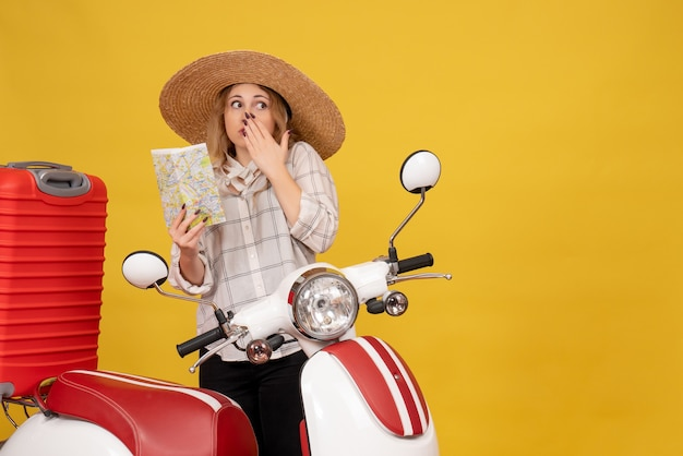 Top view of confused young woman wearing hat collecting her luggage sitting on motorcycle and holding map