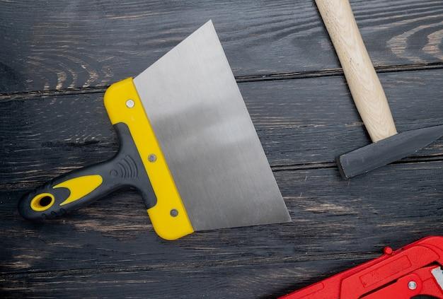 Vista superiore degli strumenti della costruzione come coltello del mastice e martello del mattone su fondo di legno
