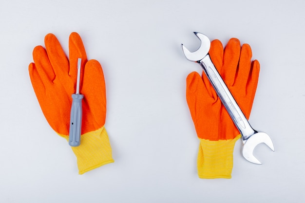 Top view of construction tools as screwdriver and open-end wrench on gloves on white background
