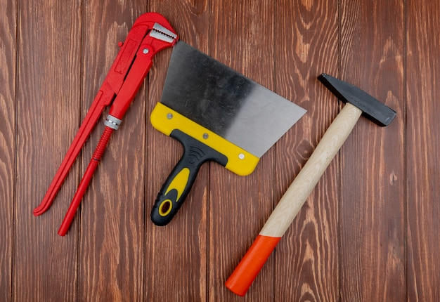 Top view of construction tools as wrench putty knife and brick hammer on wooden background