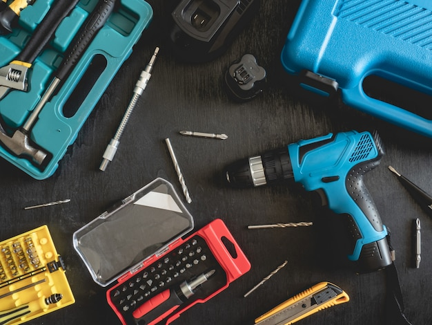 Top view of construction tools concept with drill sets, hammer, screwdriver and toolbox on black wooden background.