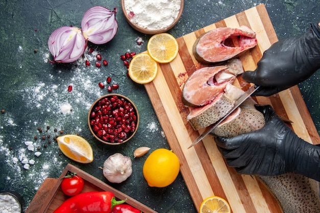 Top view cook cutting raw fish on cutting board flour bowl lemon on table