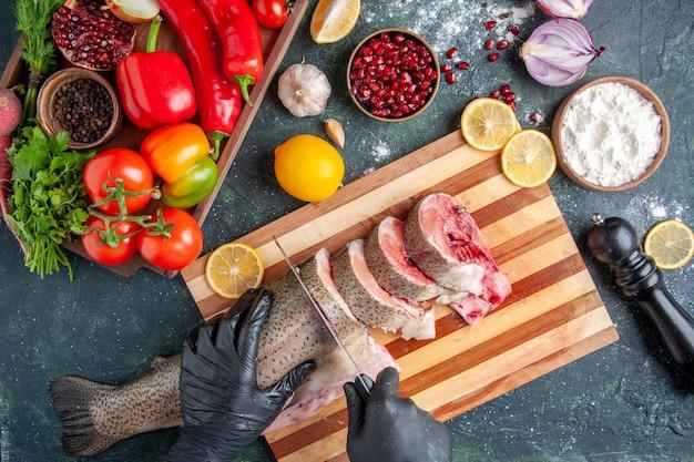 Vista dall'alto cuoco che taglia pesce crudo su tagliere verdure su tavola di legno macinapepe sul tavolo