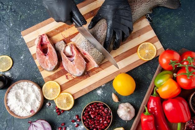 Вид сверху повар, режущий сырую рыбу на разделочной доске, миску для муки на столе