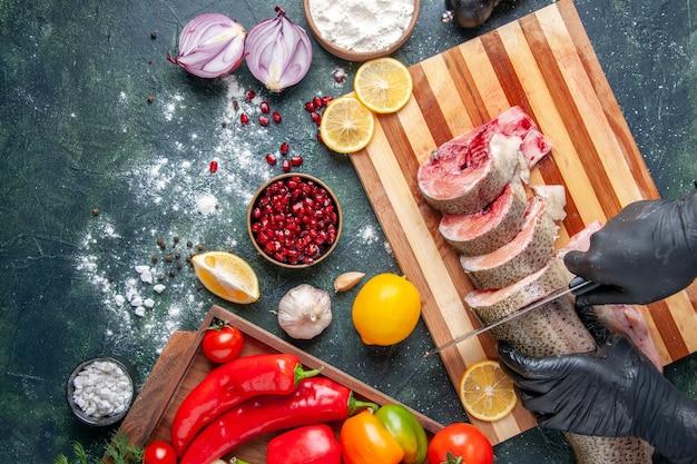 톱 뷰 요리사는 식탁에 있는 나무 판자에 야채를 도마에 올려 생선을 자르고 있습니다.