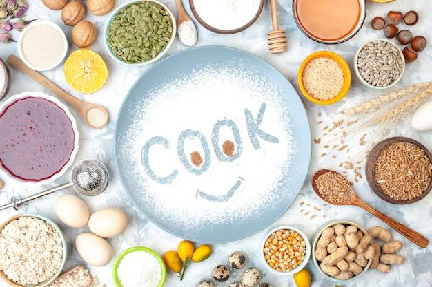 Vista dall'alto cuoco impronta su farina in polvere su ciotole piatto con semi di zucca marmellata semi di sesamo miele semi di mais arachidi uova cucchiaio di legno