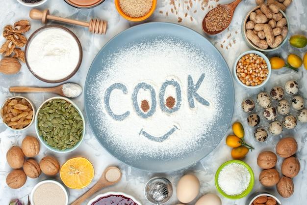 Vista dall'alto cuocere l'impronta sulla farina in polvere sul piatto e altri alimenti sul tavolo
