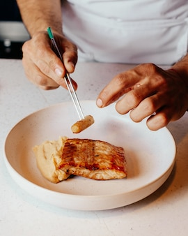 A top view cook preparing meal inside white plate and in kitchen food meal dinner cuisine