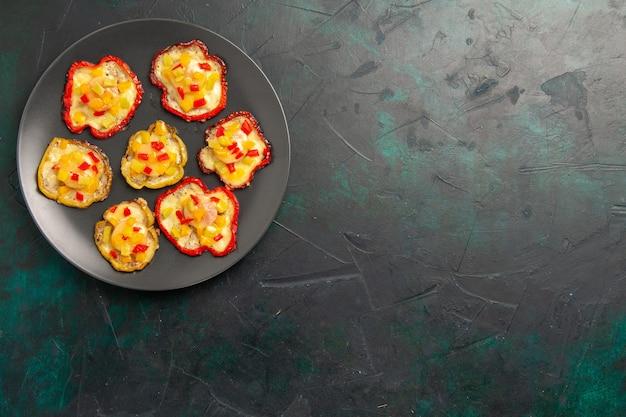 暗い表面のプレートの内側の昼食のための上面図調理されたピーマン