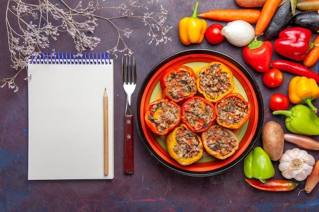 濃い灰色の表面にさまざまな調味料と野菜を使った上面図調理済みピーマン食品ドルマ野菜ミールビーフ
